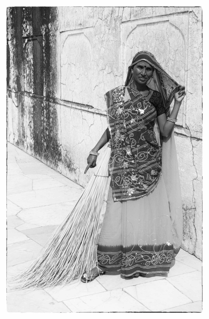 Black and white photo of lady with a broom