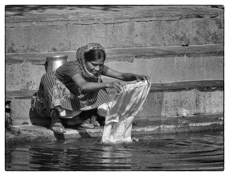Black and white photo of lady washing clothes in a lake