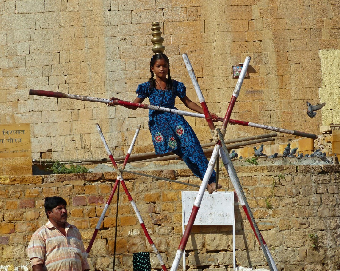 Girl in blue tunic balancing on a tightrope with man watching