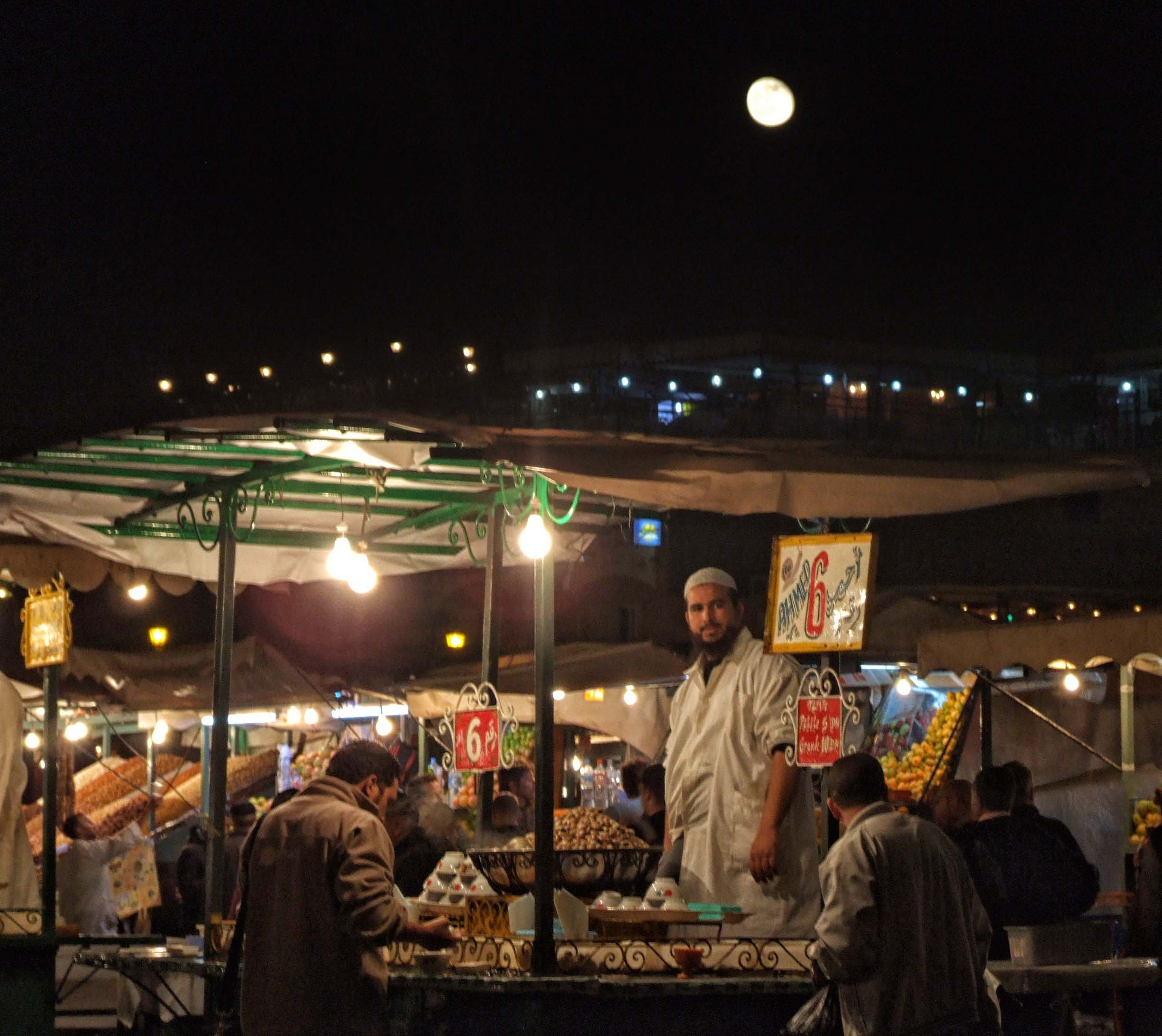 Food stalls at night with moon overhead