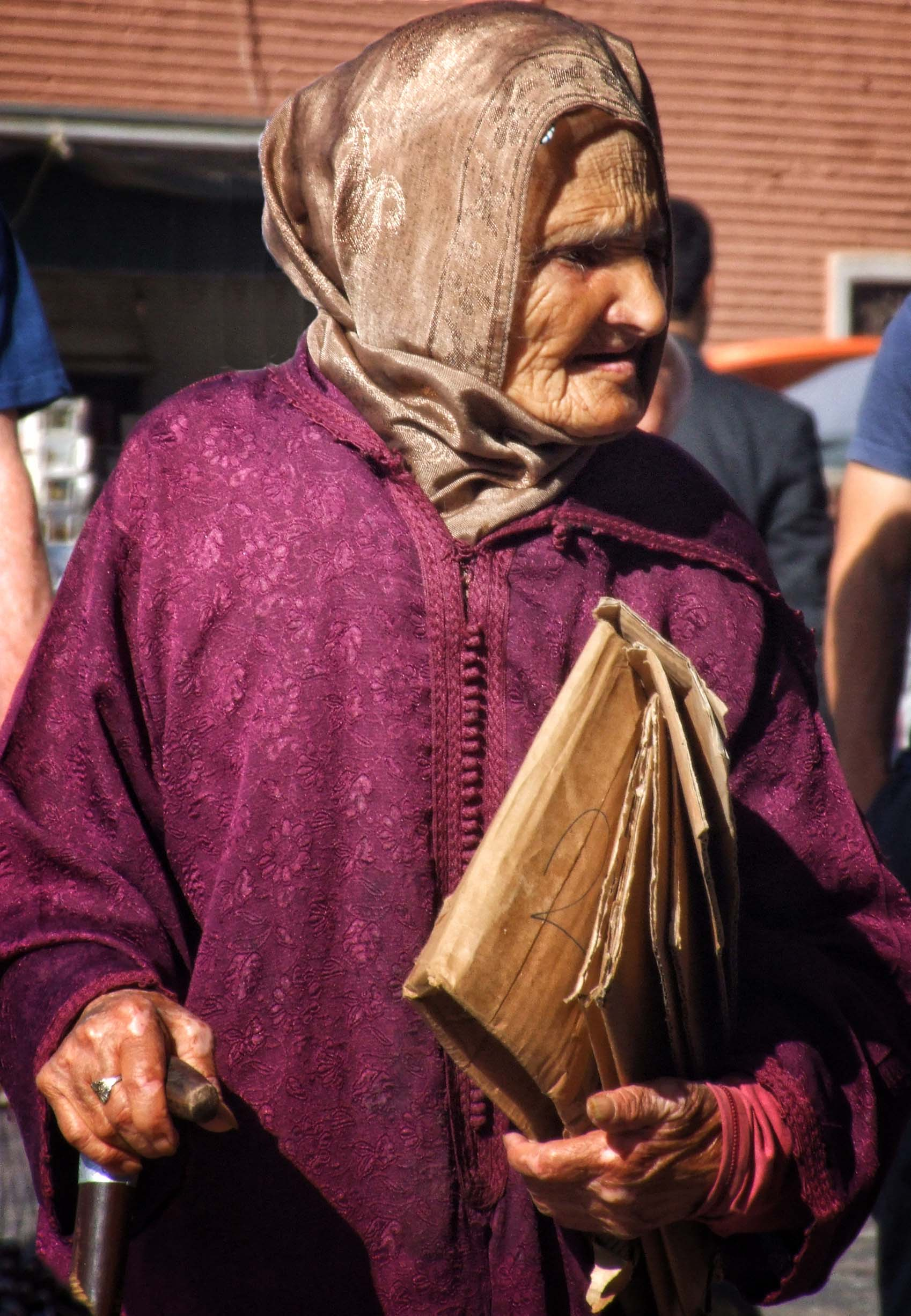 Elderly lady in purple robe and brown scarf