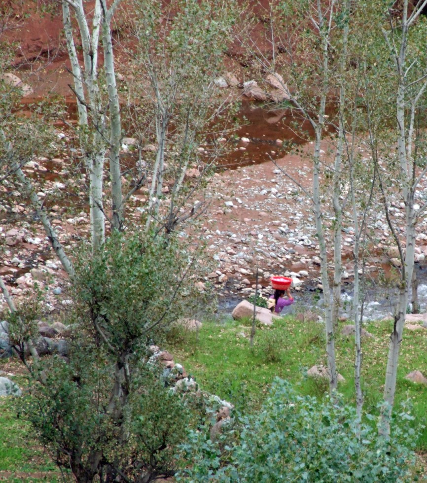 Looking down at a stream with a lady carrying a red bowl on her head