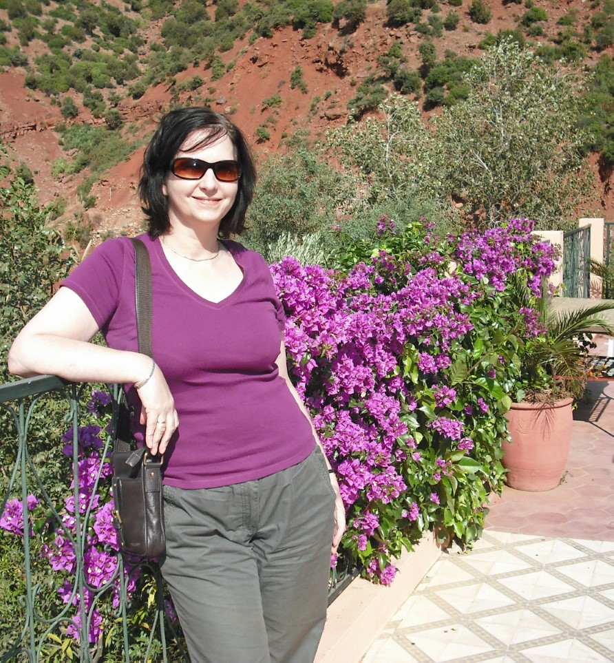 Lady in purple t-shirt on terrace by purple flowers