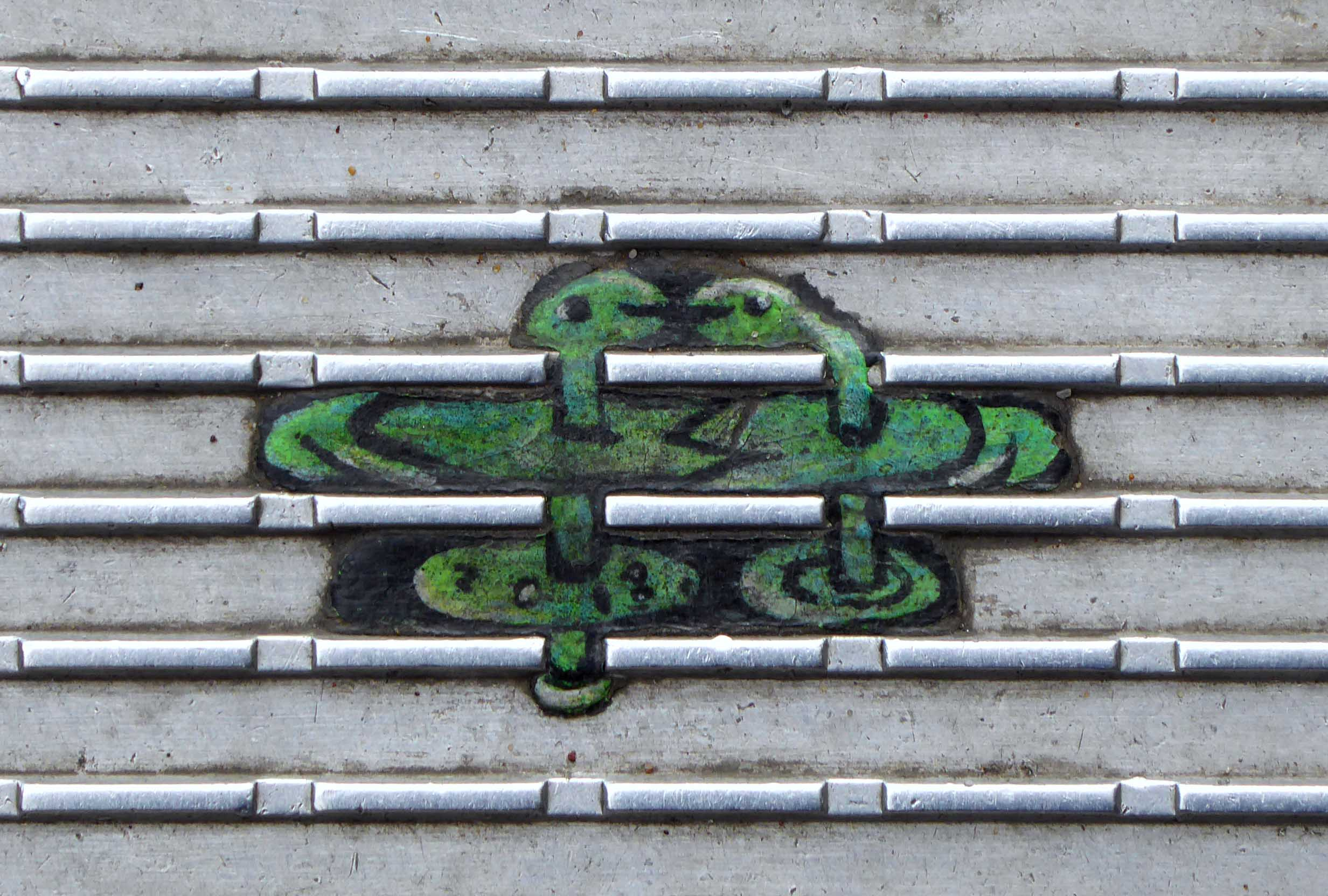 Tiny green painting on ridged metal surface