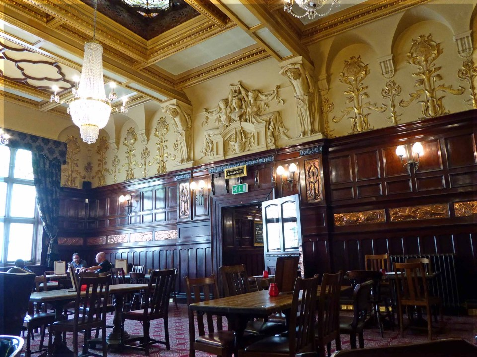 Large pub room with ornate ceiling and dark wood walls