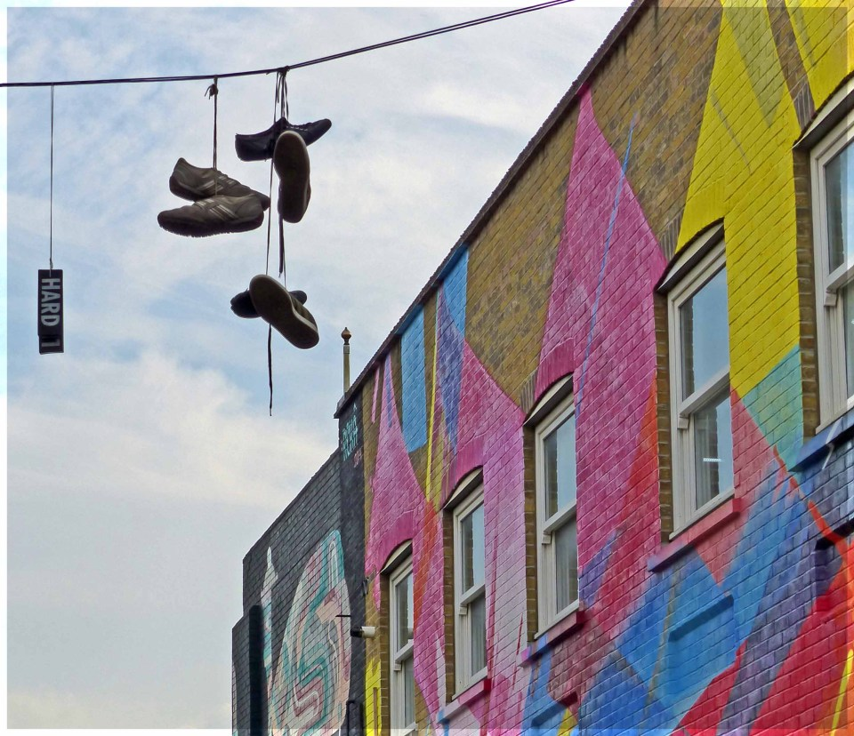 Trainers hanging from a wire and painted mural