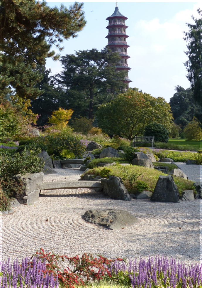 Distant view of a pagoda with rocks, gravel and low plants in front