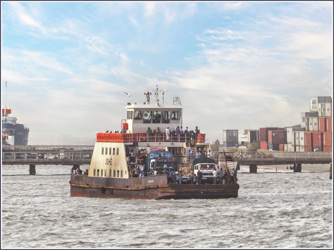 Scruffy rusting ferry with trucks and people on board