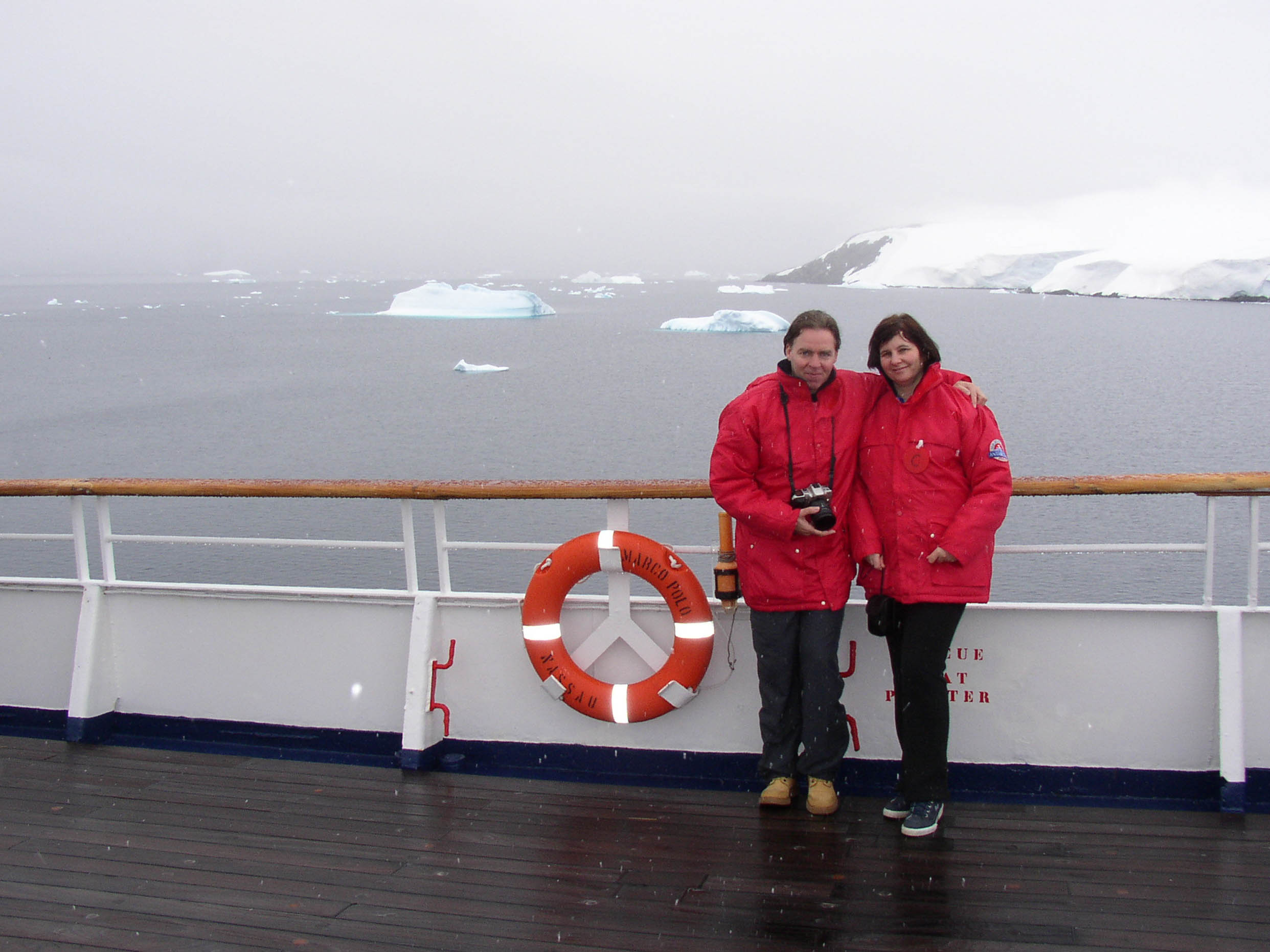 A couple wearing red anoraks on board a ship with icebergs nearby