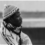 Man in knitted hat by water, black and white photo