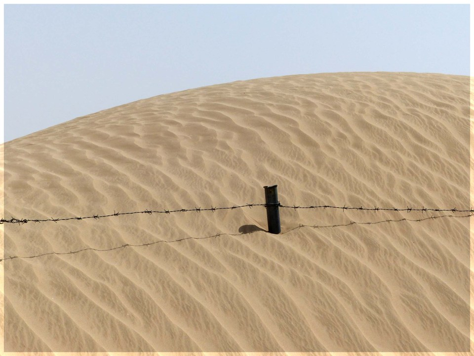 Gate post sticking out of a sand dune