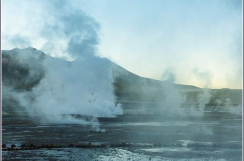 Steam rising from several geysers at sunrise
