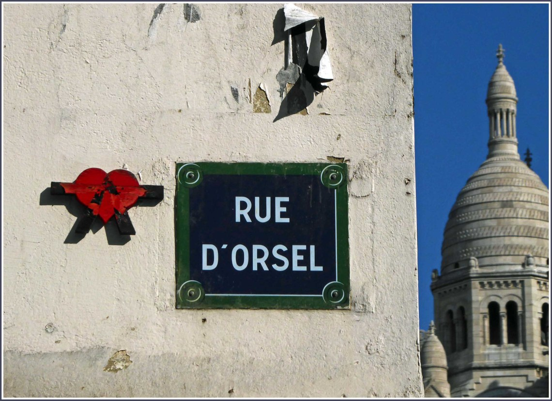 Red heart and street sign with church dome beyond
