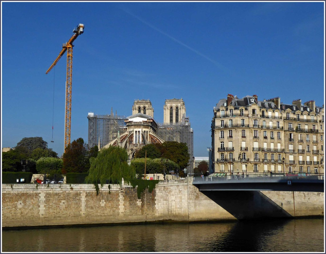 View of cathedral on far side of river, with large crane
