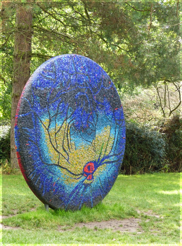 Large stone disc with blue and gold mosaic tiles