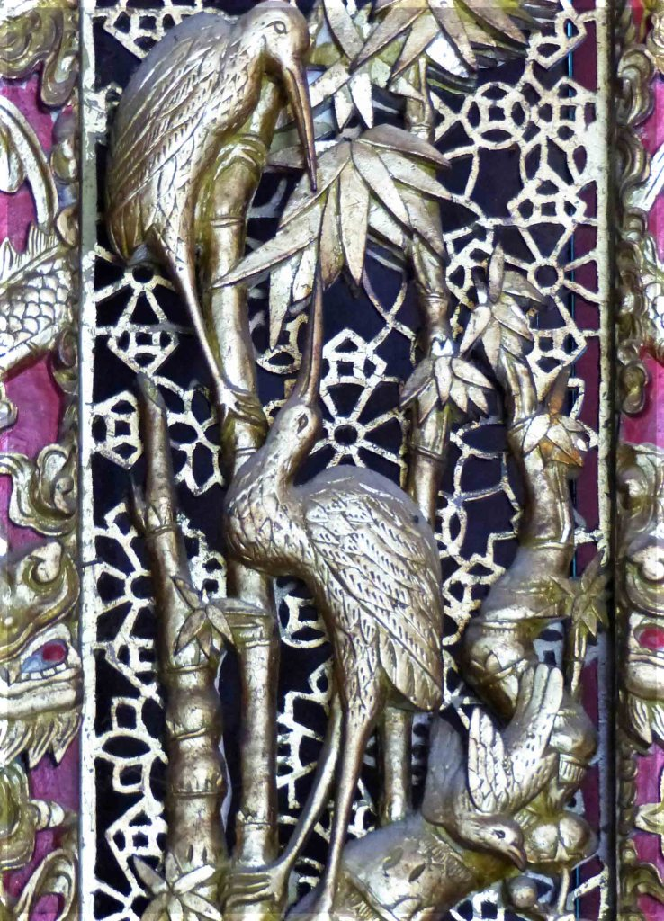Metal grille adorned with birds and bamboo