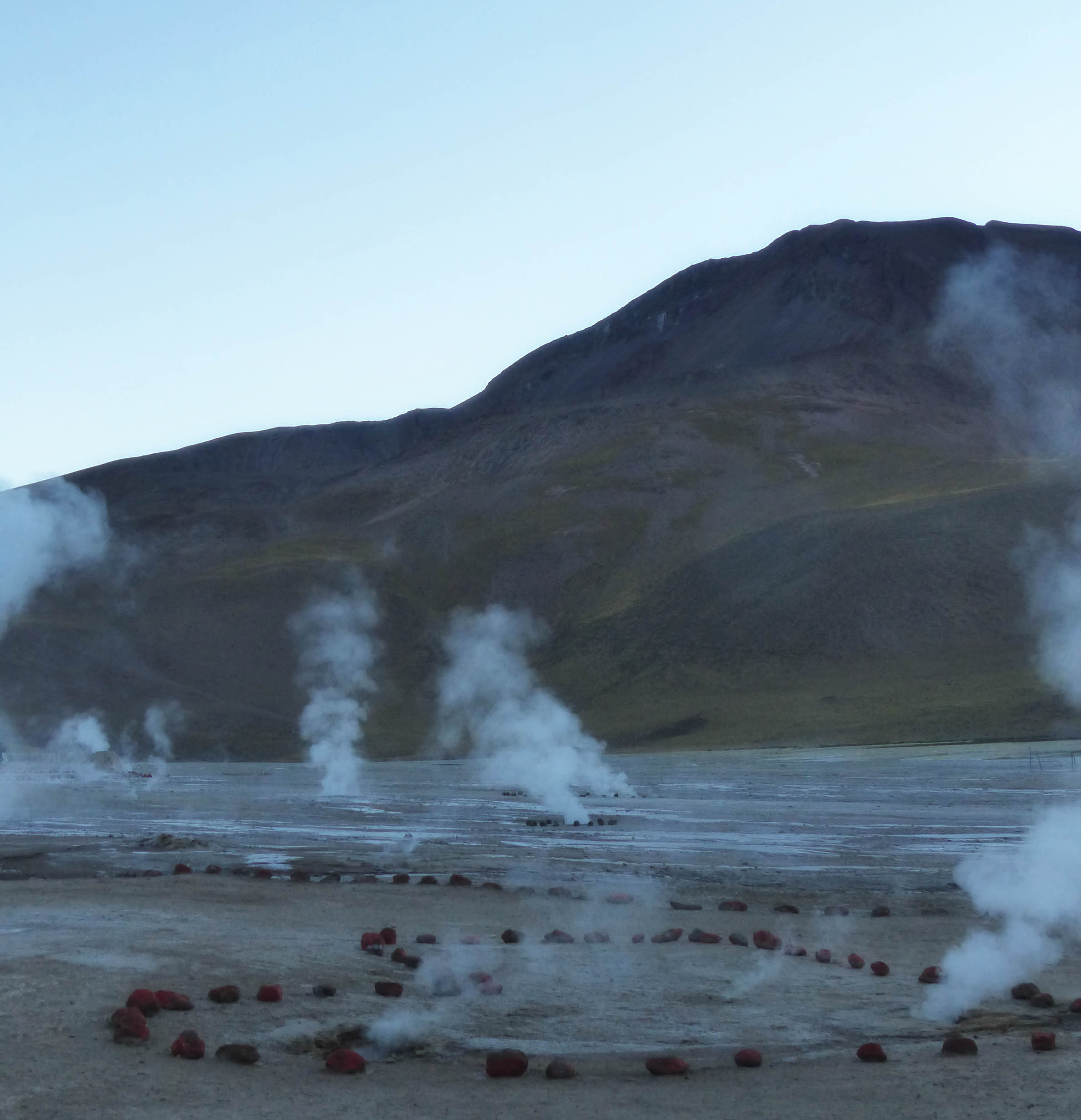 Steam rising from several geysers with mountain backdrop