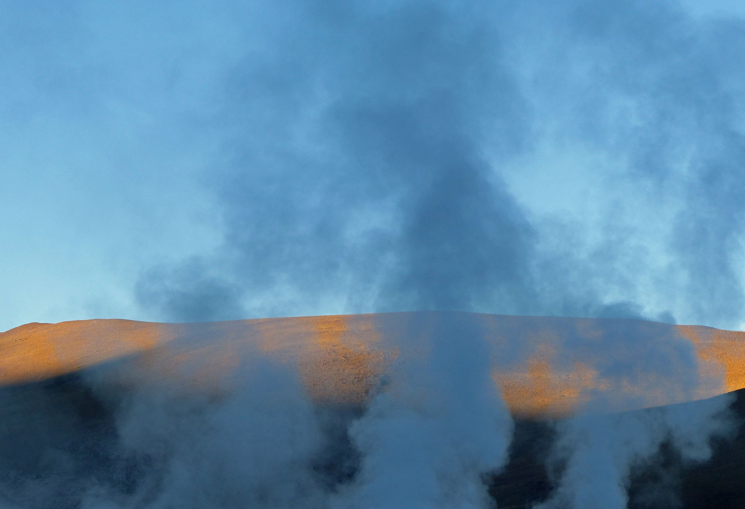 Steam rising from a geyser with sun catching hill behind