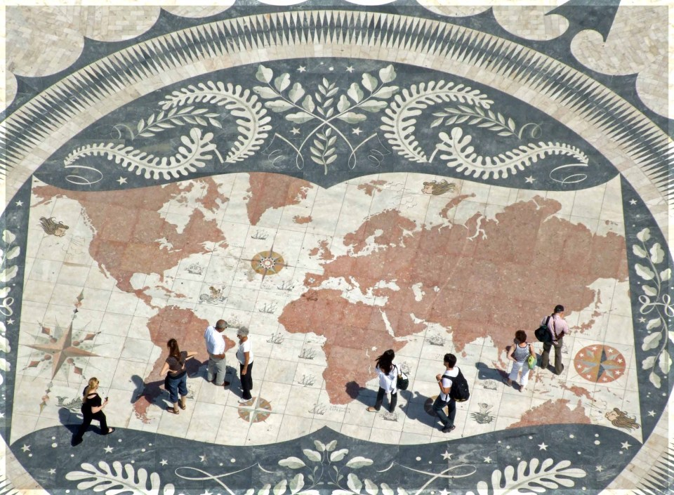 Large map of the world set in a pavement with people standing on it