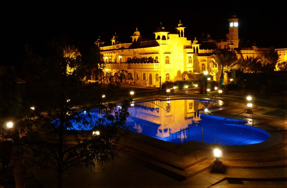 Large building with pool in front, both illuminated