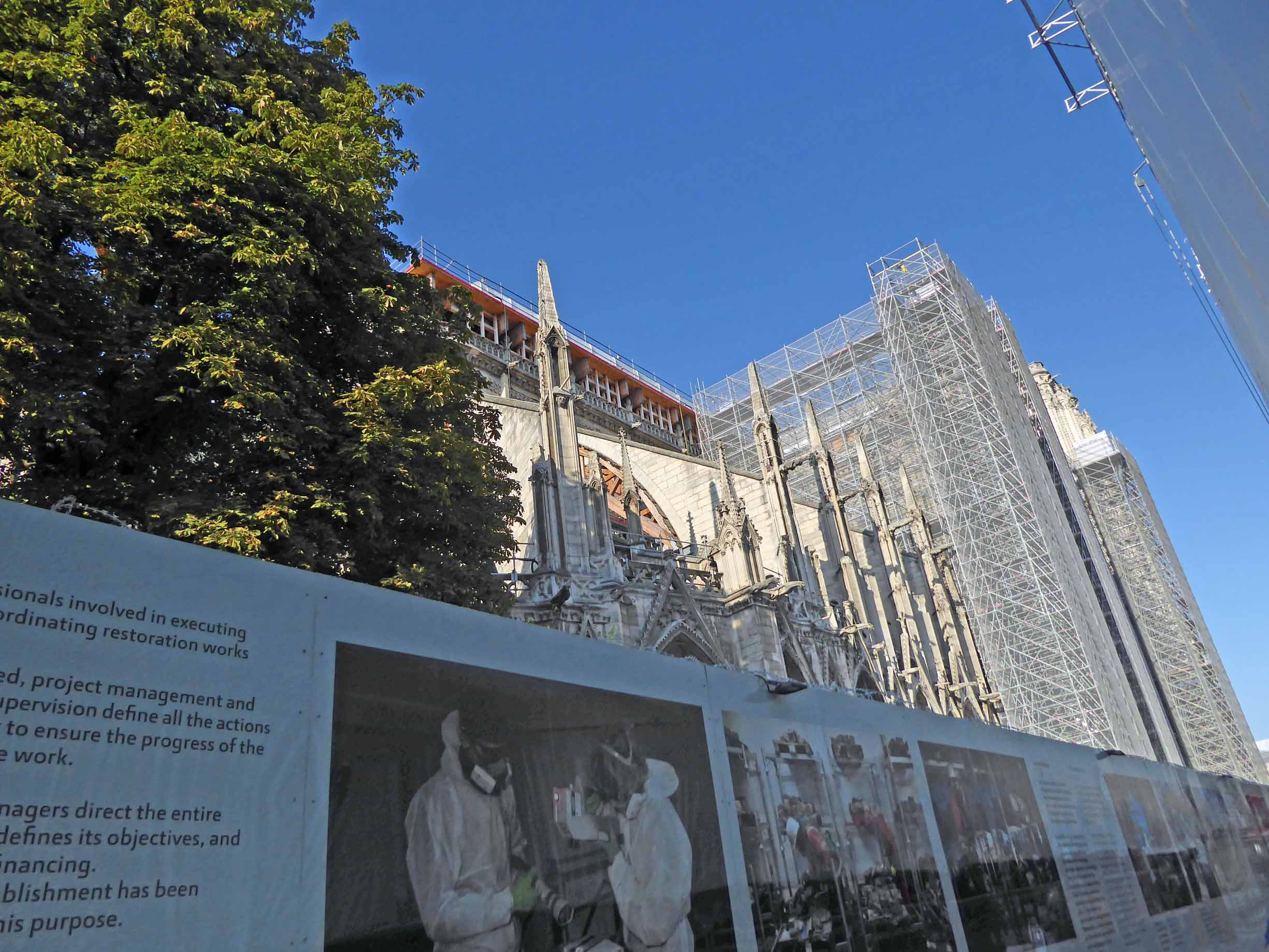 Hoarding with photos and scaffolded cathedral behind