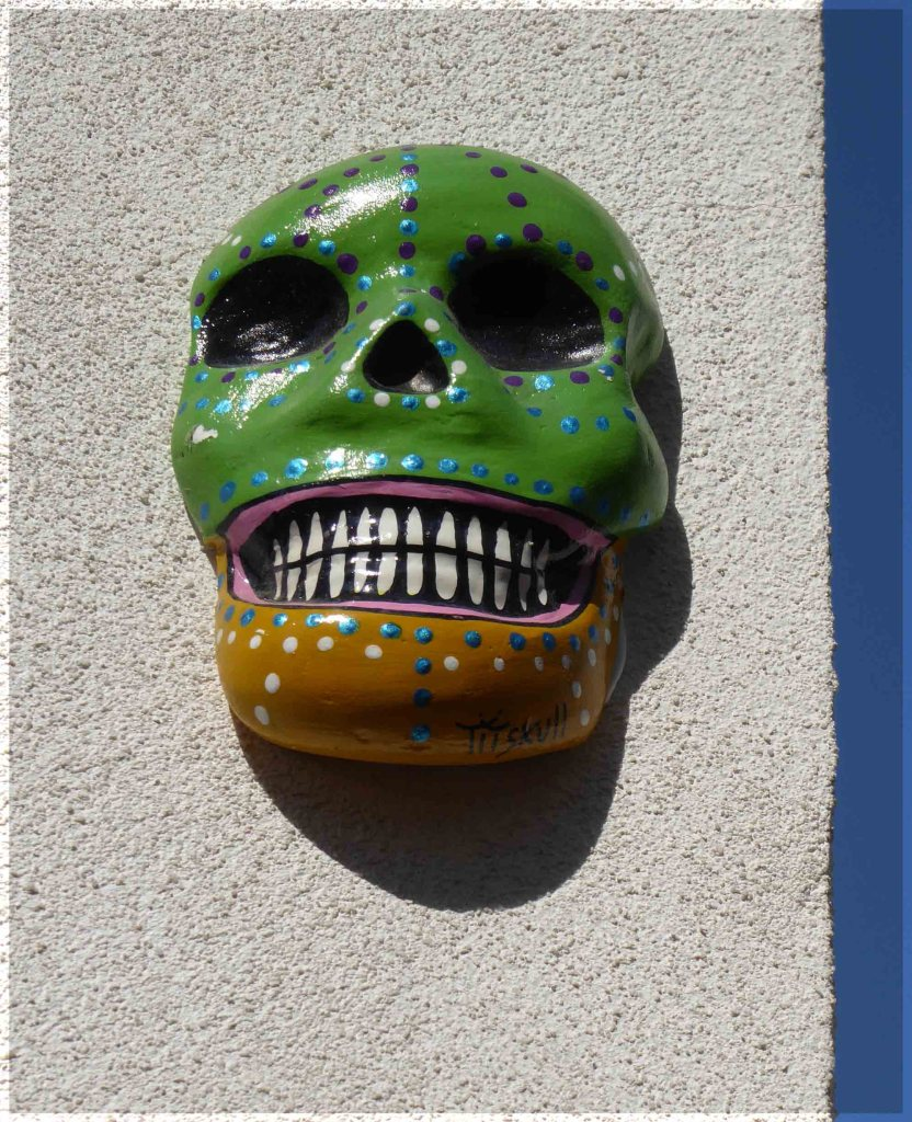 Green and tan coloured skull on a wall