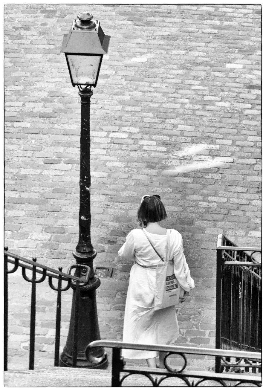Black and white photo looking down at a lady descending some steps