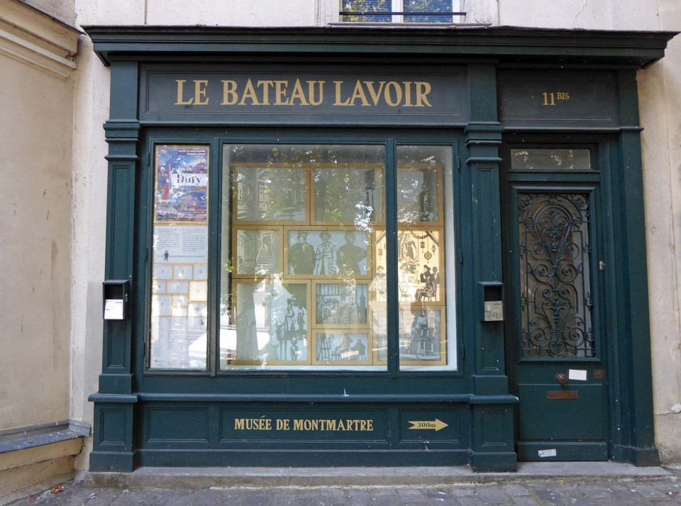 Shop front painted green with photos in window