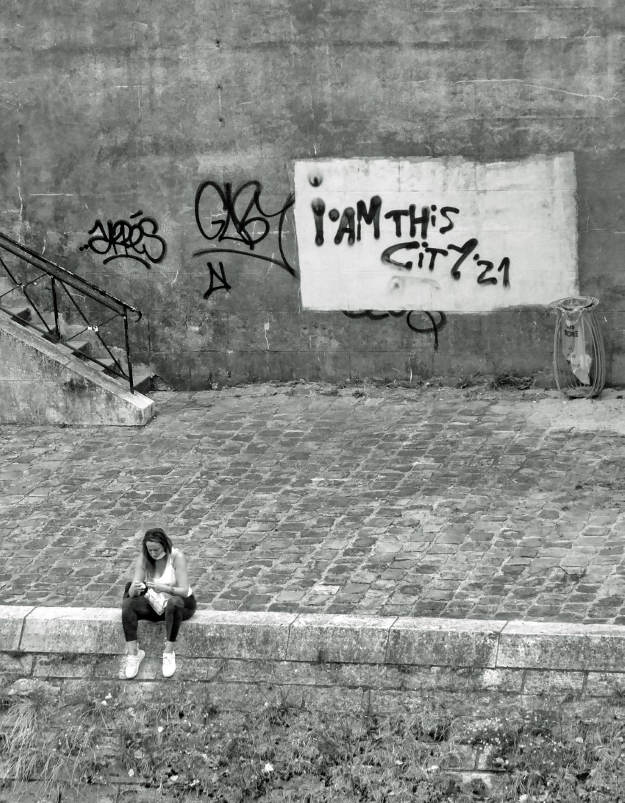 Black and white photo of a girl sitting on a stone quayside