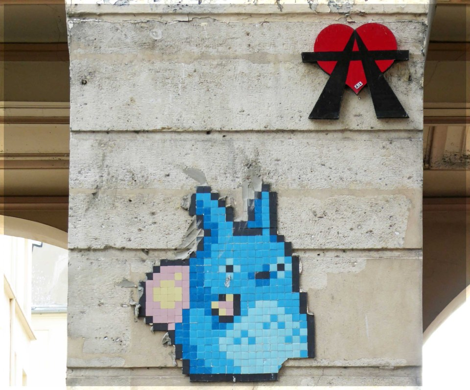 Red heart and blue mosaic animal on a wall