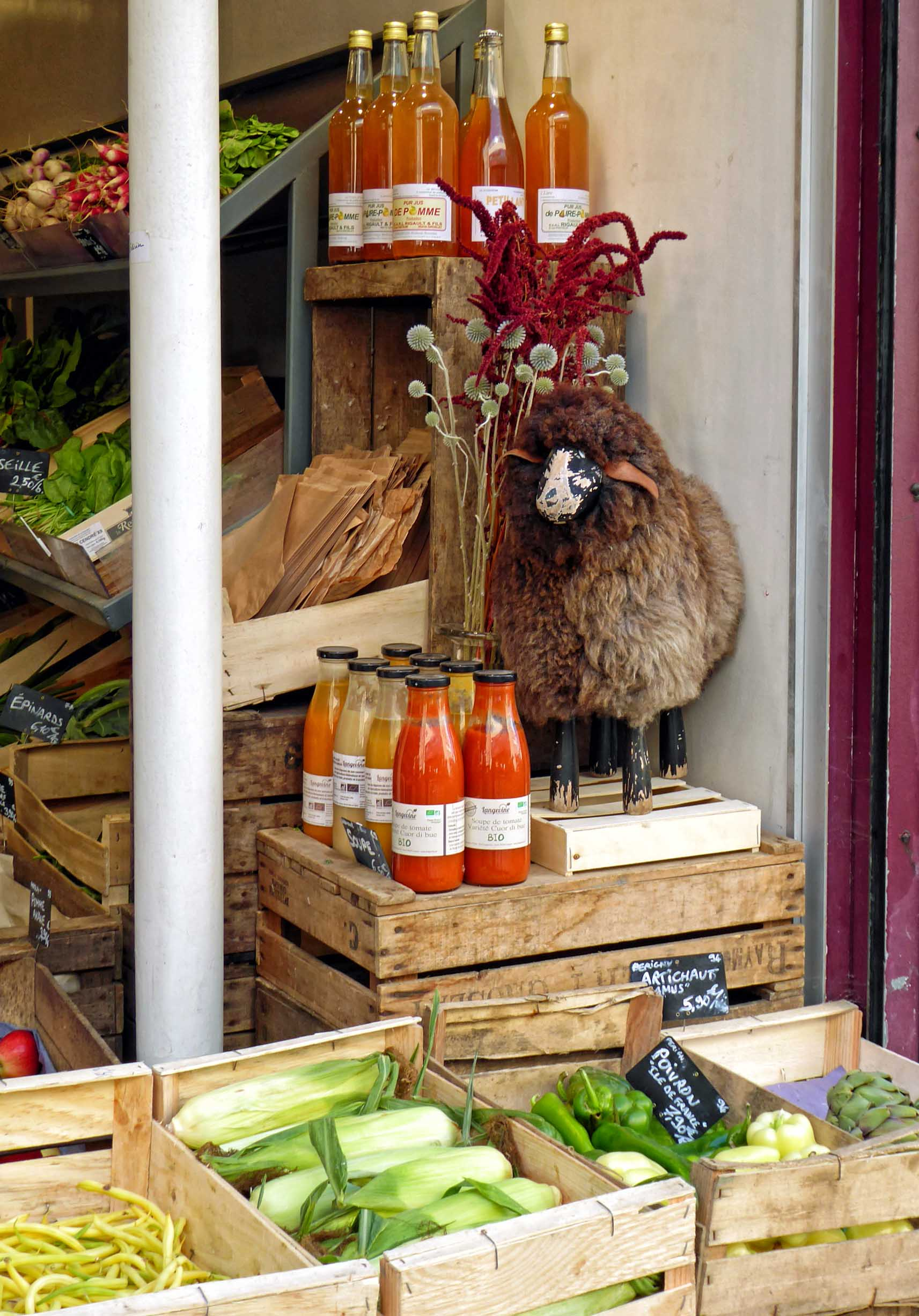 Vegetables outside a shop with a small model sheep