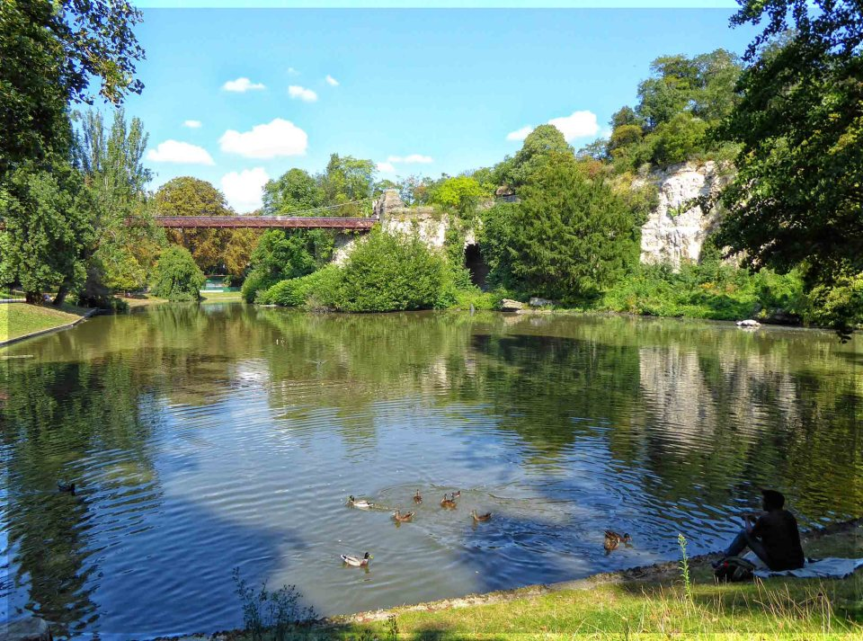 Lake with ducks and metal bridge
