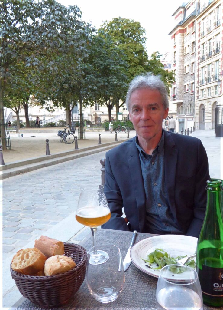 Man at a table with salad, bread and beer