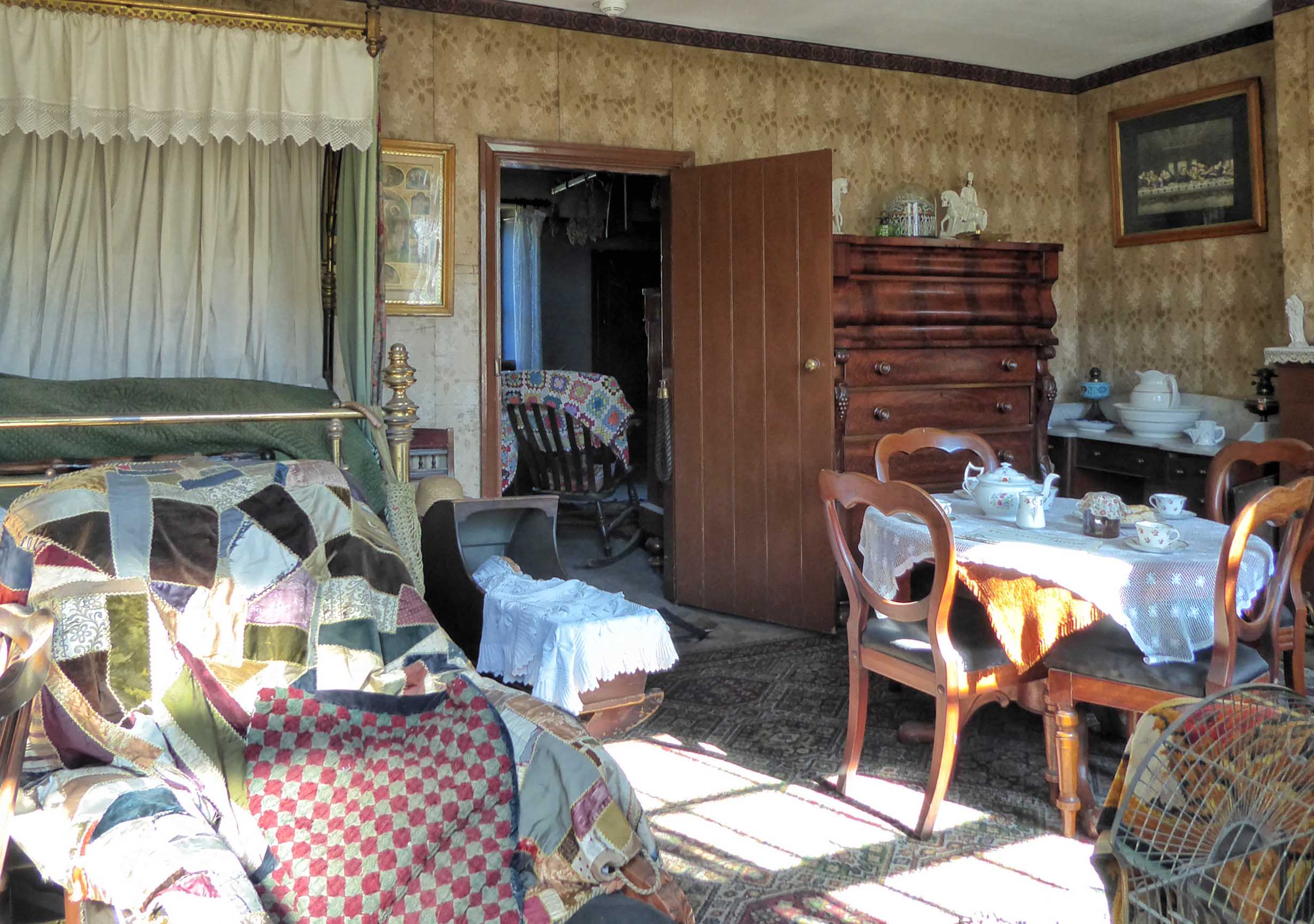 Old-fashioned sitting room with bed, cot, table and chairs