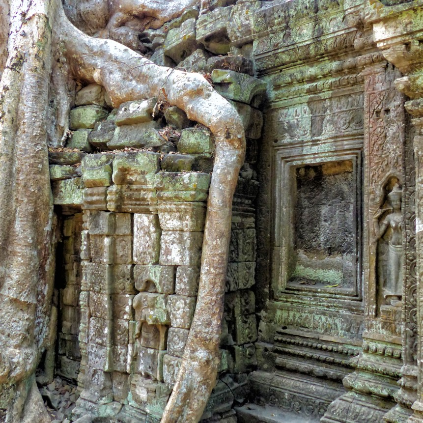 Carved stone ruin with tree roots