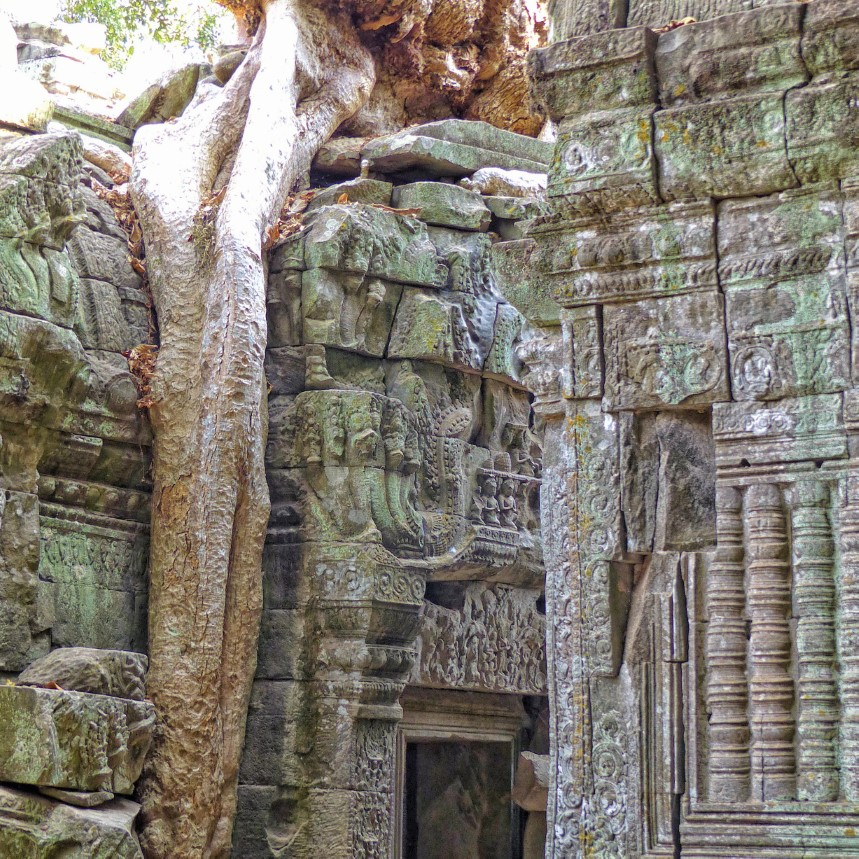Tumbledown carved stone ruin with tree roots