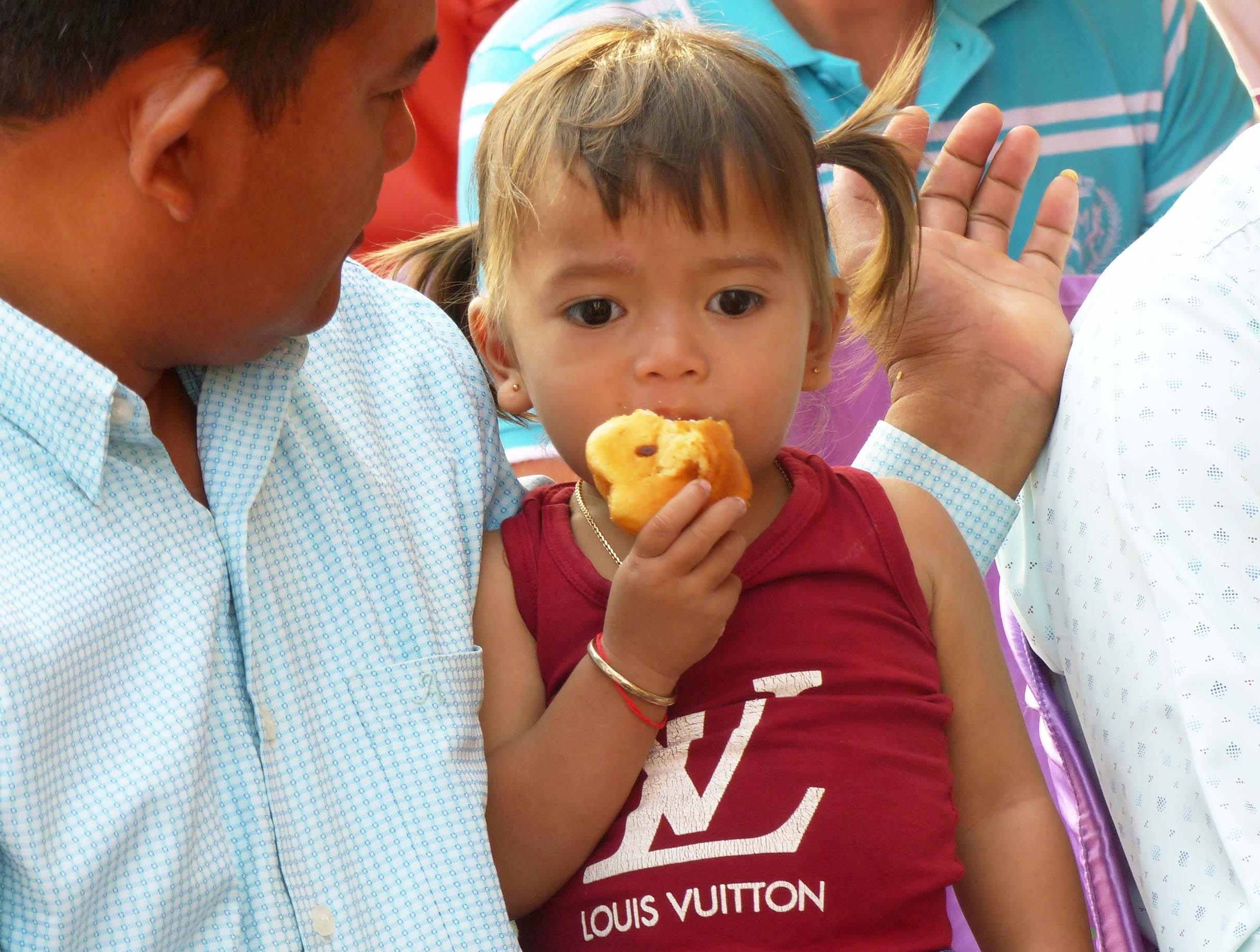 Little girl eating bread roll