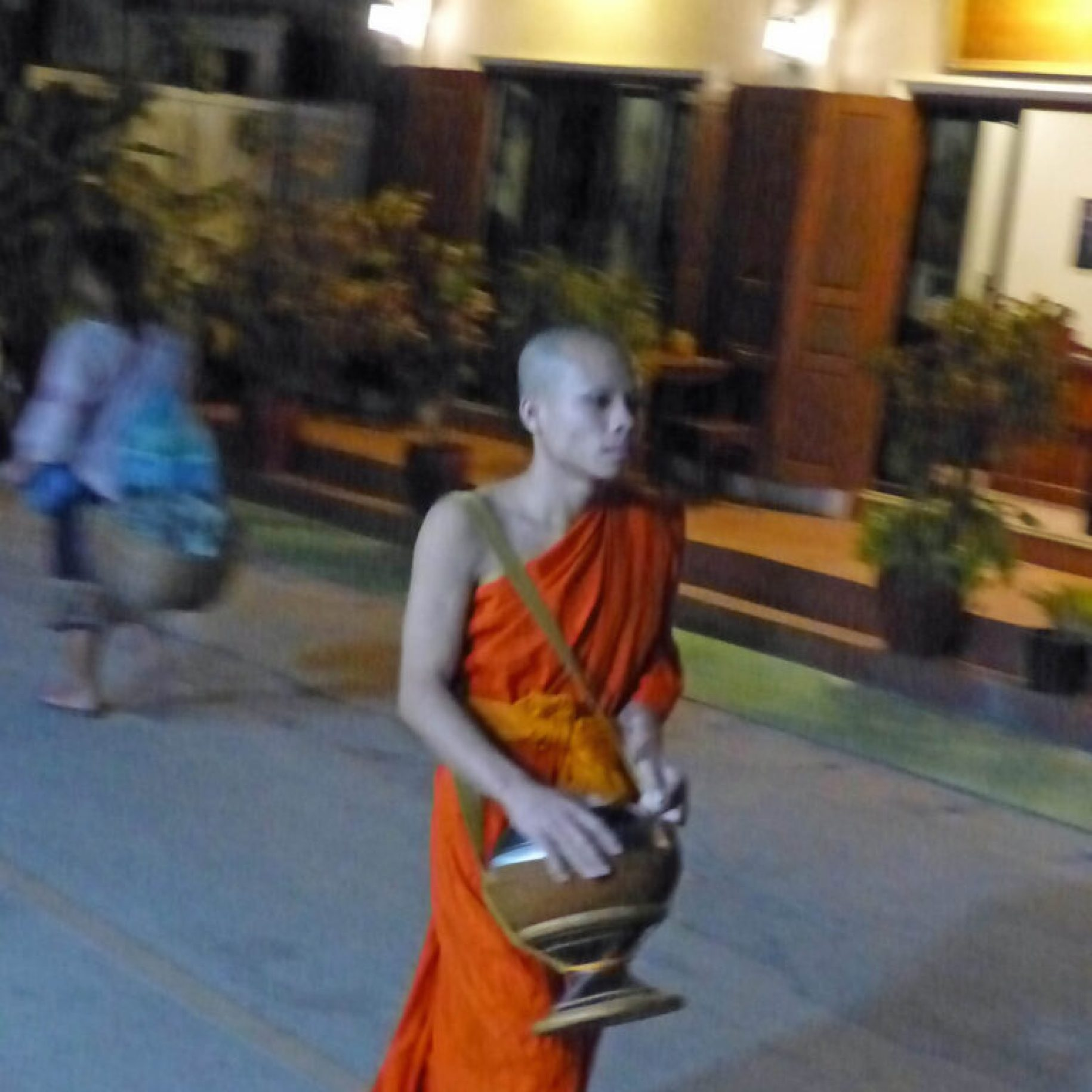 Young man in orange robes carrying a brass pot