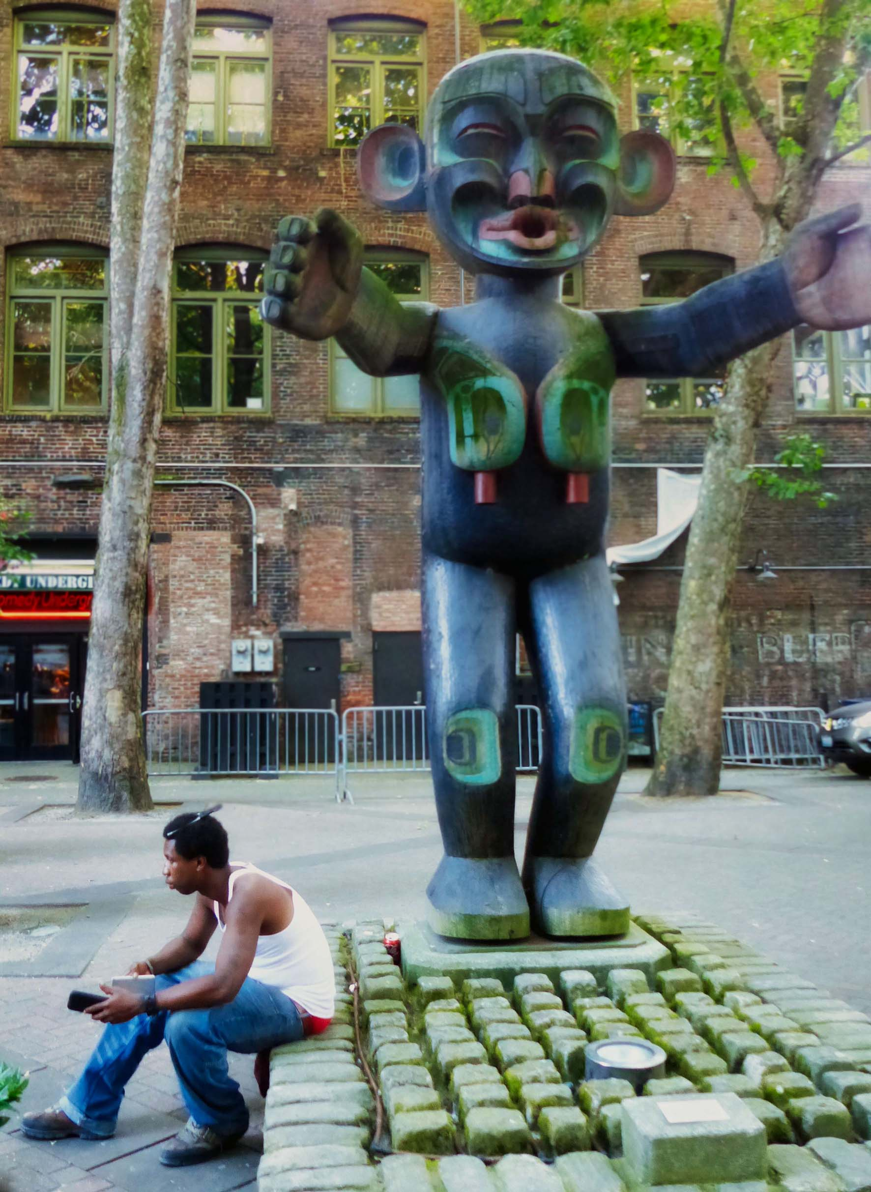 Man sitting at foot of large wooden statue