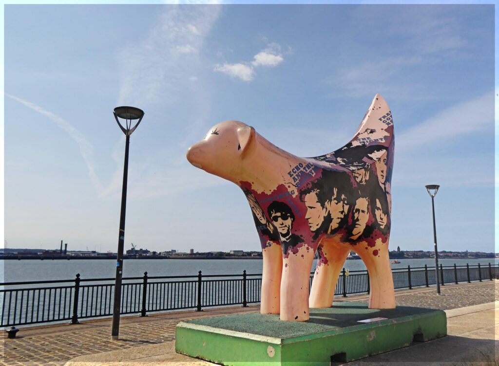 Odd large sculpture of a lamb, painted with portraits