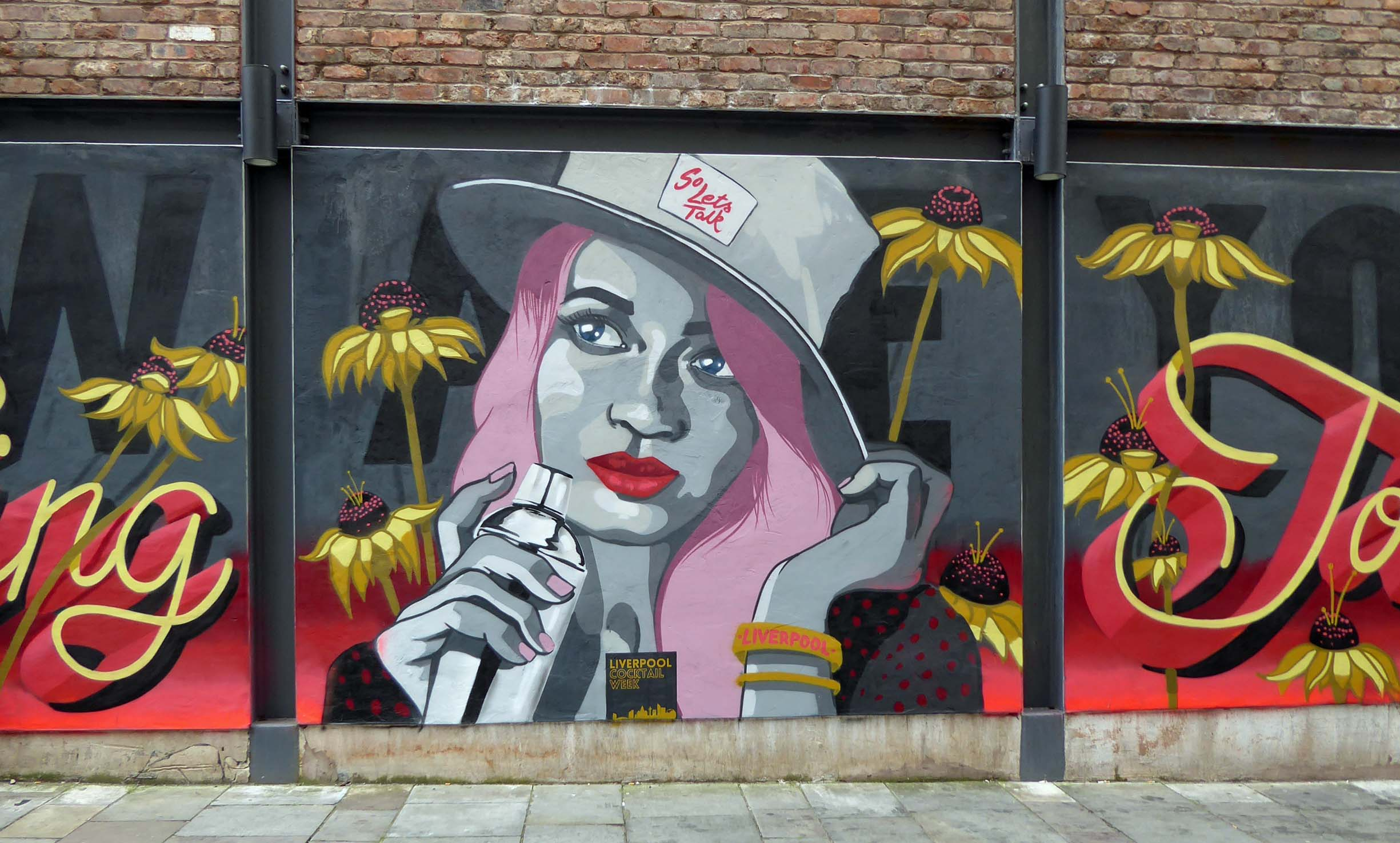 Wall painting of a woman with pink hair and cocktail shaker