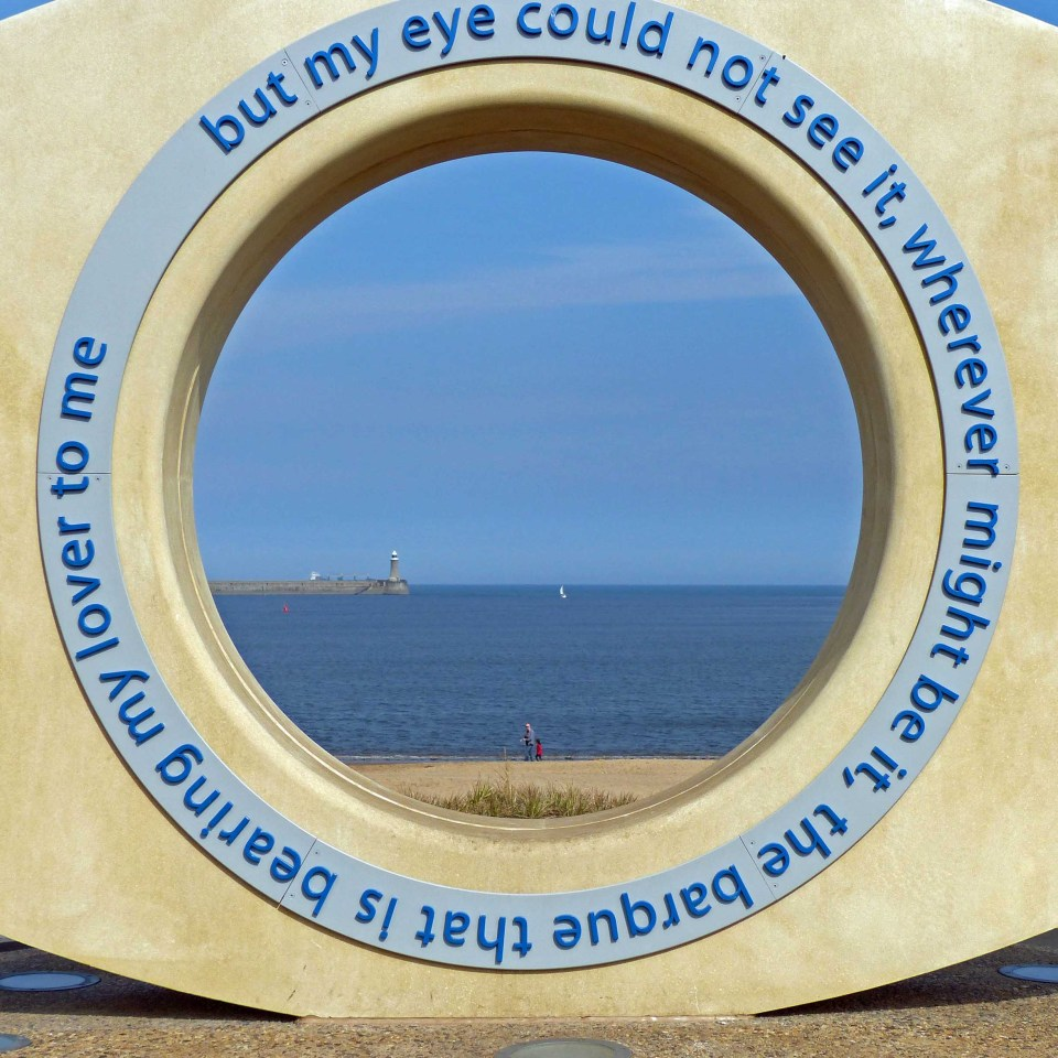 Sculpture with circular hole framing view of beach and lighthouse