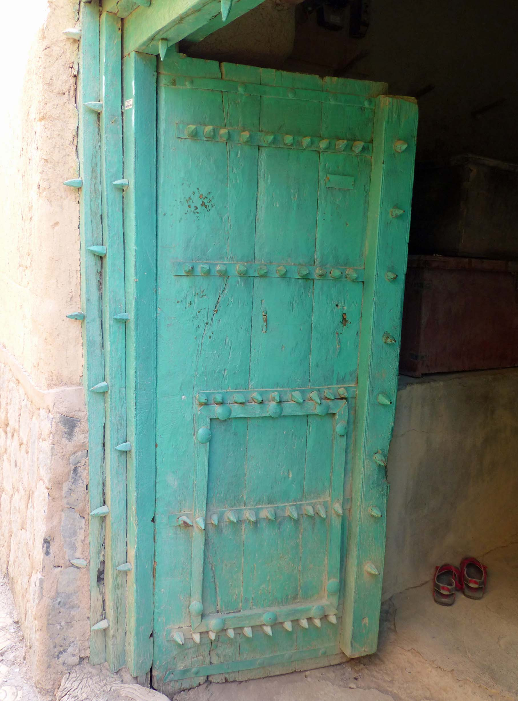 Green door propped open with glimpse of shoes inside