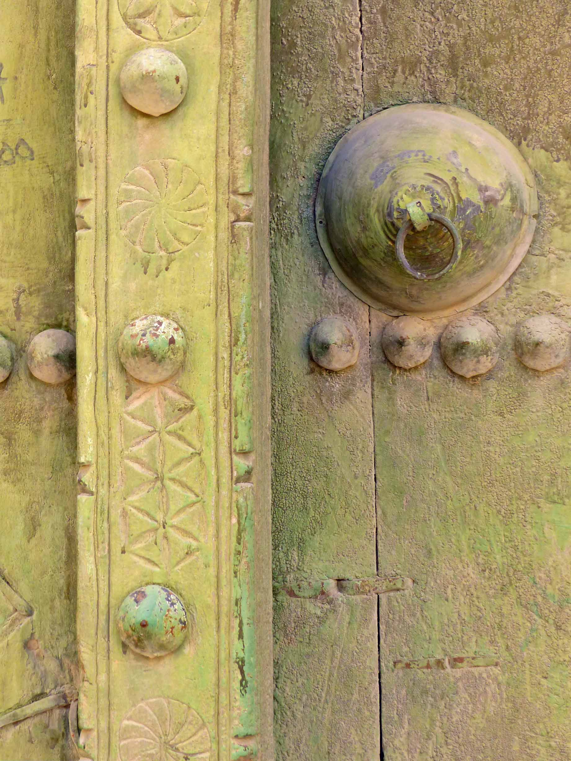 Carved wooden door painted olive green