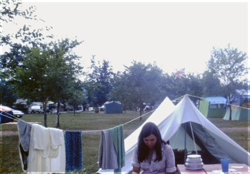 Teenage girl at a picnic table in front of a tent