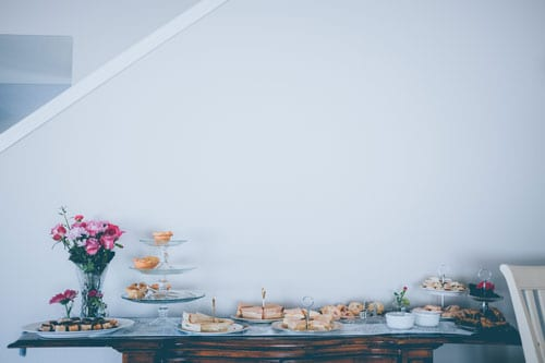 Cakes, cookies, and flowers on a table at a baby meet and greet party