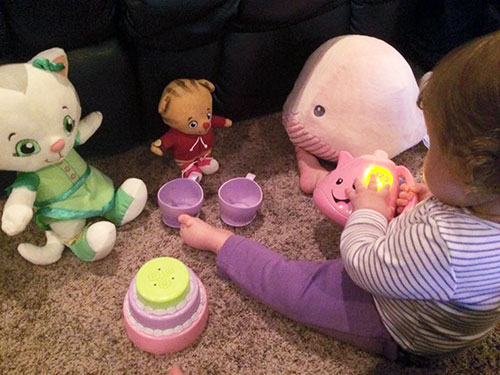 baby playing independently with stuffed animals