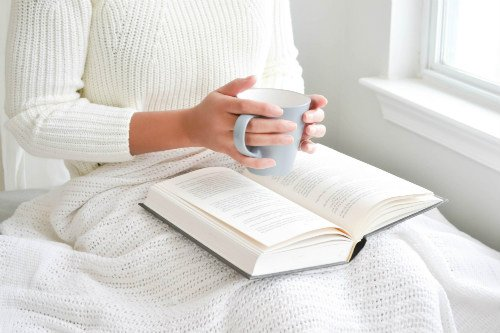 a mom enjoying a cup of coffee and a book