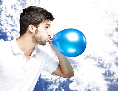 blowing a balloon