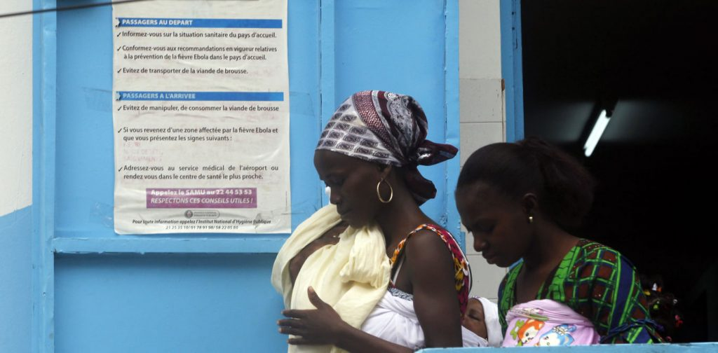Women walk near a poster displaying a government message against Ebola, at a maternity hospital in Abidjan August 14, 2014. The world's worst outbreak of Ebola has claimed the lives of 1,069 people and there are 1,975 probable and suspected cases, the vast majority in Guinea, Liberia and Sierra Leone, according to new figures from the World Health Organisation (WHO). Ivory Coast has recorded no cases of Ebola. REUTERS/Luc Gnago (IVORY COAST - Tags: HEALTH) - RTR42GHM